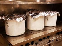 Drie grote stewpots die op hete die stovetop koken met folie, industriële keuken binnenlandse scène wordt behandeld royalty-vrije stock foto