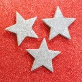 Drie grote zilveren sterren op rode achtergrond Royalty-vrije Stock Foto