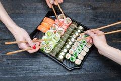 Drie handen met eetstokjes en sushireeks Zwarte houten backgrou royalty-vrije stock afbeelding