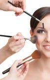 Drie handen van make-upkunstenaars die schoonheidsmiddelen toepassen stock fotografie