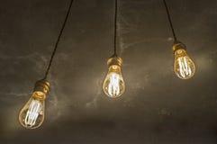 Drie hangende gloeilampen over concrete backgro van de oxyde donkere kleur Stock Fotografie