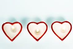 Drie hart-vormige kaarsen Stock Afbeeldingen
