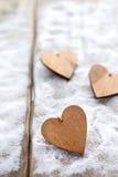 Drie harten met inschrijvingen van liefde op de achtergrond van de raad is niet de achtergrond van sneeuw, de dag van Valentine ` Stock Afbeeldingen