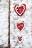 Drie harten met inschrijvingen van liefde op de achtergrond van de raad is niet de achtergrond van sneeuw, de dag van Valentine ` Royalty-vrije Stock Afbeeldingen