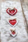 Drie harten met inschrijvingen van liefde op de achtergrond van de raad is niet de achtergrond van sneeuw, de dag van Valentine ` Royalty-vrije Stock Foto