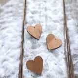 Drie harten met inschrijvingen van liefde op de achtergrond van de raad is niet de achtergrond van sneeuw, de dag van Valentine ` Royalty-vrije Stock Fotografie