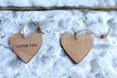 Drie harten met inschrijvingen van liefde op de achtergrond van de raad is niet de achtergrond van sneeuw, de dag van Valentine ` Royalty-vrije Stock Foto's