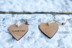 Drie harten met inschrijvingen van liefde op de achtergrond van de raad is niet de achtergrond van sneeuw, de dag van Valentine ` Stock Foto