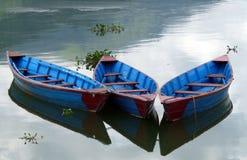 Drie heldere blauwe het roeien boten op een meer met bezinningen. Stock Afbeelding