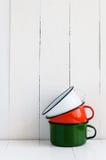 Drie heldere kleurrijke geëmailleerde mokken Stock Foto's