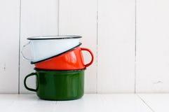 Drie heldere kleurrijke geëmailleerde mokken Stock Foto