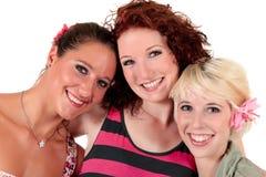 Drie het gelukkige vrouwenvrienden glimlachen Stock Afbeeldingen