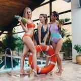 Drie het glimlachen vrouwelijke modellen die in zwempakken met ananassen en reddingsboeiring bij zwembad in luxueus hotel stellen Stock Afbeeldingen