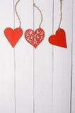 Drie houten harten op een houten lijst stock afbeelding