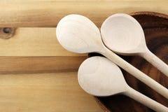 Drie houten lepels en houten plaat op gelijkaardige achtergrond Royalty-vrije Stock Afbeelding