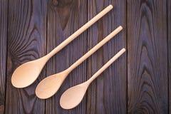 Drie houten lepels op een donkere houten lijst Stock Afbeelding