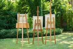 Drie houten schildersezels met schilderijen die zich op een groen gazon in een tuin of park in een concept kunst en aard bevinden royalty-vrije stock afbeelding