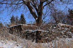 Drie houten stoelen verlaten in de sneeuw bovenop een dek in een ravijn Stock Afbeeldingen