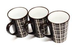 Drie identieke grote lange donkere bruine koffiekoppen met eenvoudig lijnenontwerp stock foto