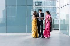 Drie Indische bedrijfsmensen die een tabletpc binnen met behulp van Royalty-vrije Stock Afbeelding