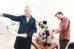 Drie ingenieurs werken met een 3d printer Een bejaarde in de voorgrond bestudeert een blauwdruk Royalty-vrije Stock Afbeeldingen