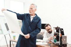 Drie ingenieurs werken met een 3d printer Een bejaarde in de voorgrond bestudeert een blauwdruk Stock Afbeelding