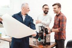 Drie ingenieurs werken met een 3d printer Een bejaarde in de voorgrond bestudeert een blauwdruk Stock Fotografie