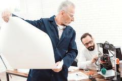 Drie ingenieurs werken met een 3d printer Een bejaarde in de voorgrond bestudeert een blauwdruk Stock Afbeeldingen