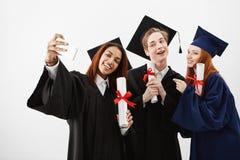 Drie internationale gediplomeerde vrienden die zich in mantels verheugen die een selfie op een telefoon maken Toekomstige advocat stock fotografie
