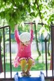 Drie jaar het oude meisje spelen bij speelplaatsdia en het hangen op dwarsbalk Stock Afbeelding