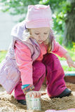 Drie jaar het oude meisje spelen met het blik van het metaaltin in speelplaatszandbak Stock Foto's