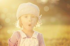 Drie jaar oud meisjes die een dwaas gezicht in backlight maken Stock Fotografie