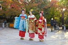 Drie Japanse meisjes die zich als Geisha in een park in Kyoto kleden Royalty-vrije Stock Fotografie
