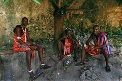 Drie jonge Afrikanen, Masai-kleding, rust in de schaduw. Stock Afbeelding