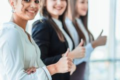 Drie jonge bedrijfsmeisjes in het bureau Het gekleed in klassieke kledingsstijl, omhoog beduimelt tonen royalty-vrije stock afbeelding
