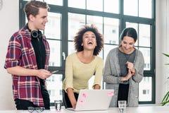 Drie jonge collega's die in de vergaderzaal lachen stock foto's