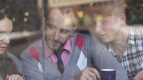 Drie jonge, creatieve en bedrijfsmensen in een koffie stock footage