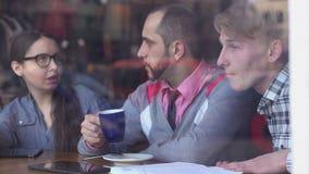 Drie jonge, creatieve mensen kwamen in een koffie samen en het bespreken van project stock video