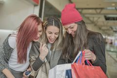 Drie jonge en mooie meisjes houden de het winkelen zakken en g stock foto
