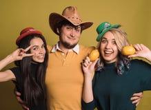 Drie jonge, en vrienden die lachen glimlachen zich verenigen koesteren De studio schoot in de gele muur Stock Afbeelding