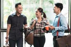 Drie jonge en vrolijke werknemers op het hun werk die in de ochtend spreken royalty-vrije stock afbeelding