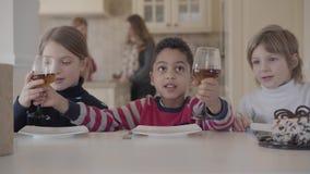 Drie jonge geitjes bij de lijst met kleine cake en sapglazen terwijl twee cijfers van vrouwen die op de achtergrond spreken Twee stock video