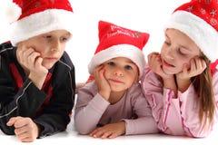 Drie jonge geitjes in de Kerstmiskappen Stock Fotografie