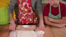 Drie jonge geitjes die deeg voor pizza kneden stock footage