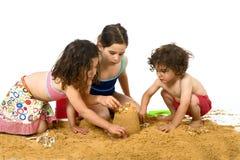 Drie jonge geitjes die in het zand spelen Royalty-vrije Stock Afbeeldingen