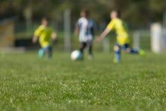 Drie jonge geitjes die voetbal spelen Royalty-vrije Stock Foto