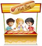 Drie jonge geitjes in een hotdogtribune Stock Fotografie