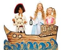 Drie jonge geitjes, piraat en prinses op kartonschip Stock Foto's