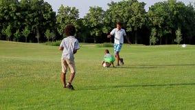 Drie jonge geitjes spelen voetbal stock footage
