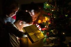 Drie jonge geitjes, twee peuterjongens en een meisje, die een gouden gift B openen stock afbeeldingen